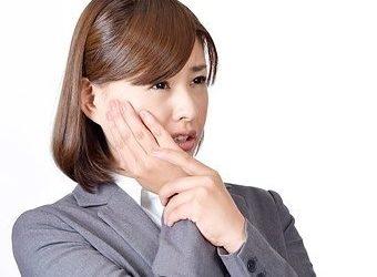 歯が痛くて頬に手を置く女性